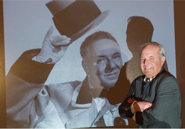 Ron standing next to a projected image on screen of his grandfather.