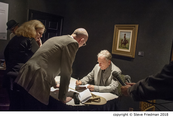 Candid photo of Dick Cavett sitting at a table signing a book with two people standing and leaning over to watch him.